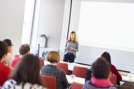 スピーカーは、大学の講堂でプレゼンテーションを行います。参加者は講義を聴くと、ノートを作るします。 写真素材