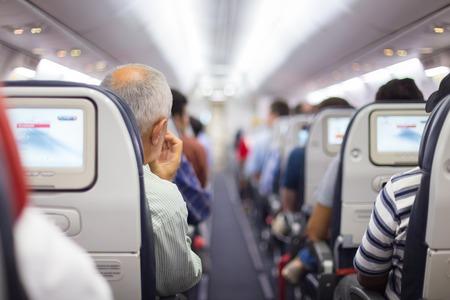 uvnitř: Interiér letadla s cestujícími na sedadlech, které čekají na promluvit off.