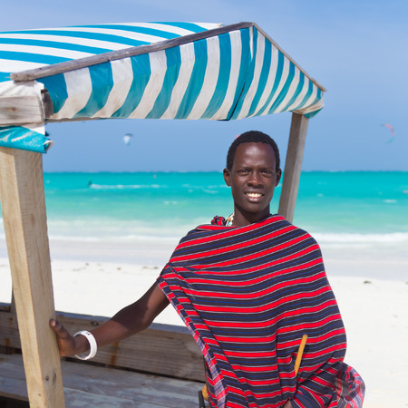 adult kenya: Traditonaly dressed black man on the beach. Maasai warrior on picture perfect tropical sandy beach on Zanzibar, Tanzania, East Africa.