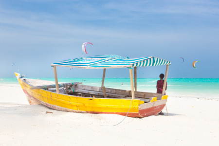 adult kenya: Maasai warrior lounging aroundon traditional colorful wooden boat on picture perfect tropical sandy beach on Zanzibar, Tanzania, East Africa. Kiteboarding spot on Paje beach.
