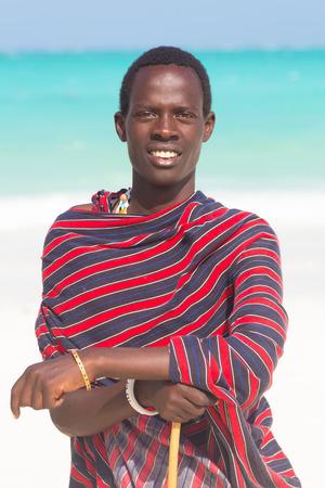 warrior tribal: Traditonaly dressed black man on the beach. Maasai warrior on picture perfect tropical sandy beach on Zanzibar, Tanzania, East Africa.