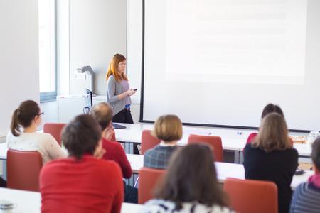 the speaker: Altavoz que da la presentaci�n en el sal�n de conferencias en la universidad. Los participantes de escuchar conferencias y tomando notas. Copiar espacio para la marca en la pantalla blanca.