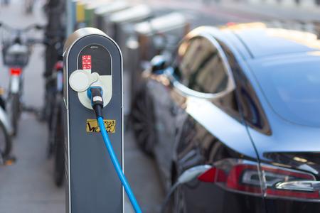 電気自動車を充電するための電源装置。 駅を充電する電気自動車。電気自動車充電中に差し込まれている電源のクローズ アップ。 報道画像