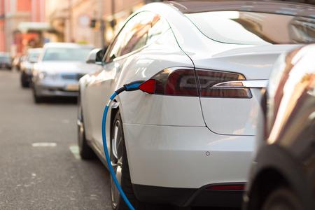 Voeding voor elektrische auto opladen. Elektrische auto laadstation. Close-up van de voeding aangesloten op een elektrische auto wordt opgeladen. Redactioneel