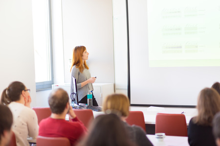 Speaker giving presentation in lecture hall at university. Participants listening to lecture and making notes. Copy space for brand on white screen.