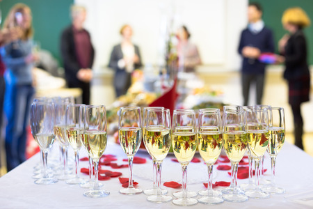 Banquet event. Waiter pouring champagne into glass. Table with the wineglasses, snacks and cocktails.