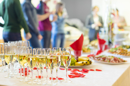 Banquet event. Table with the wineglasses, snacks and cocktails.