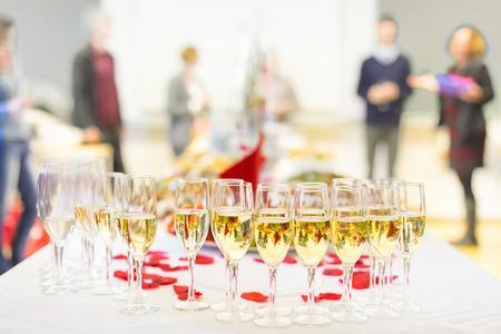 socializando: Evento de Banquetes. Tabla con las copas, aperitivos y cócteles. Gente que celebra en el fondo.