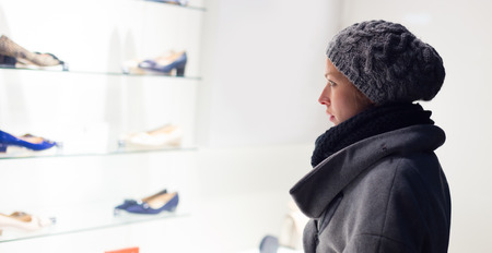 casualy: Casualy winter dressed lady window shopping in front of sinfully expensive boutique store dispaly window. Customer woman in shopping street, looking at window, outdoor.