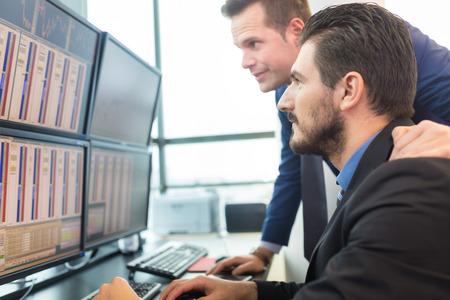 stock traders: Gli uomini d'affari negoziazione titoli. Commercianti di riserva guardando i grafici, gli indici e numeri su pi� schermi di computer. I colleghi in discussione in ufficio commercianti.