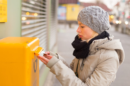 Young woman posting a letter, dropping an envelope in a postbox.