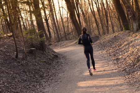 trails: Lady running in the forest.  Running woman. Female runner jogging during outdoor workout in a Nature. Fitness model outdoors. Weight Loss. Healthy lifestyle.