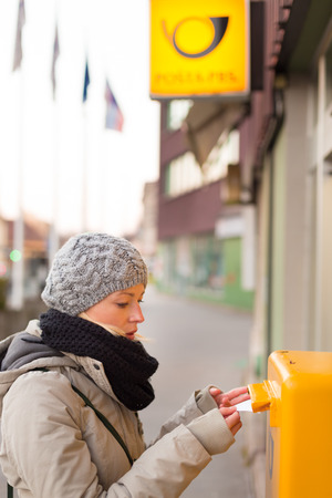 sender: Young woman posting a letter, dropping an envelope in a postbox.