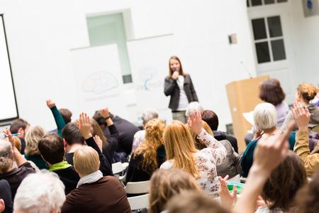 estudiantes universitarios: Tengo una pregunta. Grupo de personas sentadas en las sillas de la sala de conferencias, levantando sus manos. Taller en la universidad. Negocios y Emprendimiento evento.
