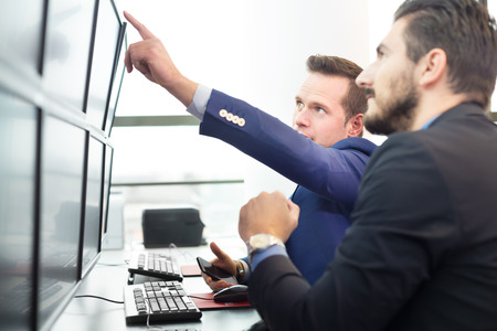 investor: Businessmen trading stocks. Stock traders looking at graphs, indexes and numbers on multiple computer screens. Colleagues in discussion in traders office.