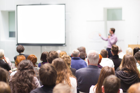 Speaker Giving a Talk at Business Meeting. Audience in the conference hall. Business and Entrepreneurship. Copy space on white board.