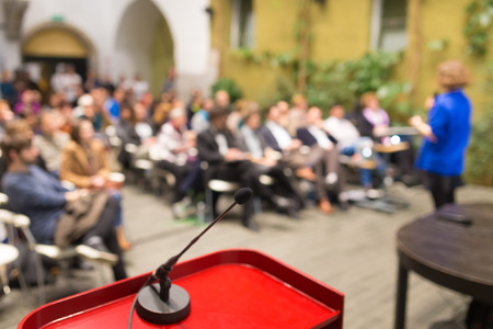 conference audience: Female speaker at Business Conference. Audience at the conference hall. Business and Entrepreneurship. Business woman. Focus on microphone. Stock Photo