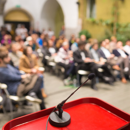 Microphone on a Podium Desk at Business Event. Audience at the conference hall. Business and Entrepreneurship. Business woman. Focus on microphone. photo