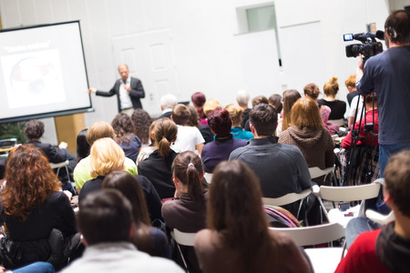 corporate group: Speaker Giving a Talk at Business Meeting. Audience in the conference hall. Business and Entrepreneurship. Copy space on white board.