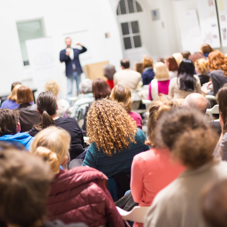 Luidspreker met een gesprek op zakelijke bijeenkomst. Publiek in de conferentiezaal. Bedrijfsleven en ondernemerschap. Exemplaar ruimte op wit bord. Stockfoto