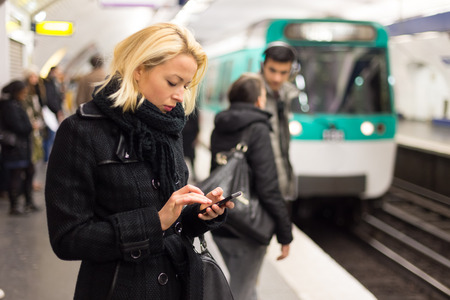 arrive: Young woman in winter coat with a cell phone in her hand waiting on the platform of a railway station for train to arrive. Public transport. Stock Photo