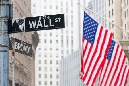 Wall street sign in New York with American flags and New York Stock Exchange background. 에디토리얼