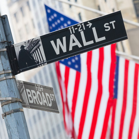 public market sign: Wall street sign in New York with American flags and New York Stock Exchange background. Editorial