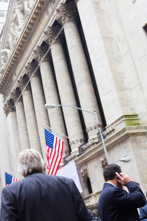 moneymaker: Businessman talking on the phone on Wall street in New York with American flags and New York Stock Exchange in background.