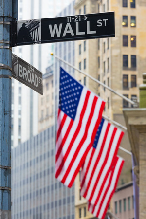 dow: Wall street sign in New York with American flags and New York Stock Exchange background. Editorial