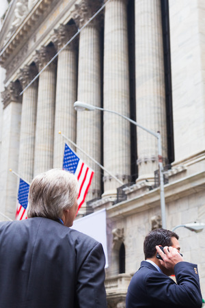 new york stock exchange: Businessman talking on the phone on Wall street in New York with American flags and New York Stock Exchange in background.