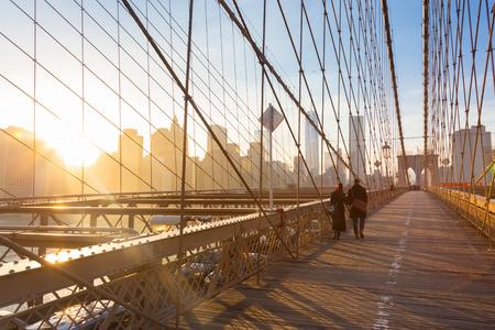 pedestrian bridge: Couple walking on pedestrian path across Brooklyn bridge. New York City Manhattan downtown skyline in sunset with skyscrapers illuminated over East River panorama as seen from Brooklyn bridge.