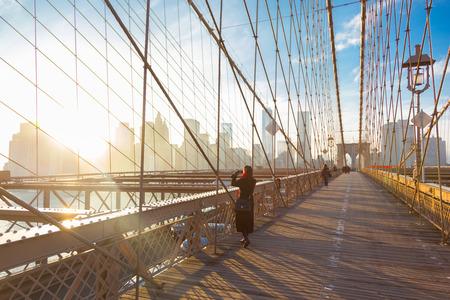 Vrouw die een foto van de Brooklyn Bridge. New York City Manhattan skyline van het centrum in zonsondergang met wolkenkrabbers verlicht dan East River panorama gezien vanaf de Brooklyn Bridge. Stockfoto