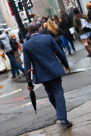 moneymaker: Businessman wearing umbrella, walking crowded streets of Manhattan, New York City, United States of America. Stock Photo