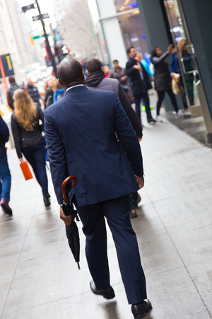 moneymaker: Businessman wearing umbrella, walking crowded sidewalk of Manhattan, New York City, United States of America. Stock Photo