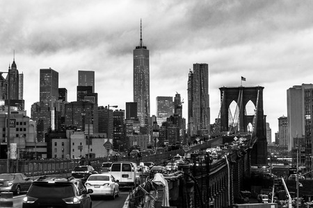panorama city panorama: Traffic on Brooklyn bridge and New York City Manhattan downtown skyline at dusk with skyscrapers over East River panorama. Black and white.