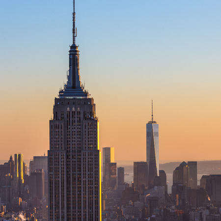 empire state building: New York City. Manhattan downtown skyline with illuminated Empire State Building and skyscrapers at sunset seen from Top of the Rock observation deck. Square composition. Editorial