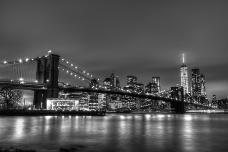 manhattan bridge: Brooklyn bridge and New York City Manhattan downtown skyline at dusk with skyscrapers illuminated over East River panorama. Copy space. Black and white image.