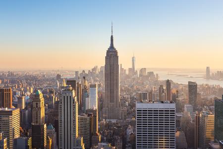 Cidade de Nova York. Skyline do centro de Manhattan com o Empire State Building iluminado e arranha-céus ao pôr do sol, visto do topo da plataforma de observação da rocha. Composição vertical. Foto de archivo
