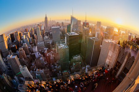 eye traveller: New York City. Manhattan downtown skyline with illuminated Empire State Building and skyscrapers at sunset seen from Top of the Rock observation deck. Vertical composition Fish eye lens shot.