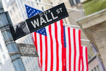 new york stock exchange: Wall street segno a New York con le bandiere americane e lo sfondo di New York Stock Exchange.