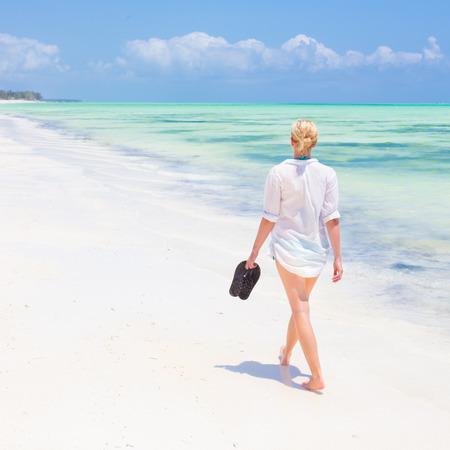 flipflops: Caucasian woman walking joyfully on tropical beach. Beautiful caucasian model  wearing white beach tunic on vacations walking down picture perfect Paje beach, Zanzibar, Tanzania. Copy space. Stock Photo