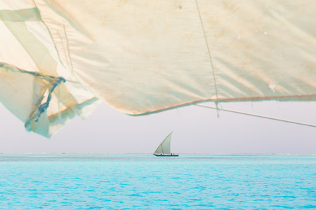 afrika: Traditional wooden sailboat sailing on a horizon of turquoise blue sea of Zanzibar, Tanzania, Afrika. Stock Photo