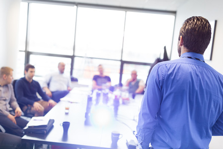 interaction: Business man making a presentation at office. Business executive delivering a presentation to his colleagues during meeting or in-house business training, explaining business plans to his employees. Stock Photo