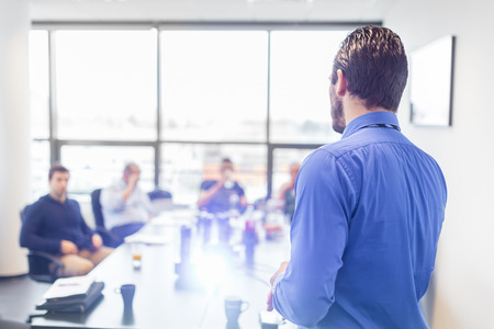 Business man making a presentation at office. Business executive delivering a presentation to his colleagues during meeting or in-house business training, explaining business plans to his employees. Standard-Bild