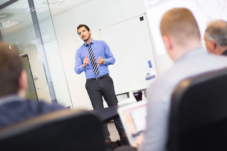 businessperson: Business man making a presentation at office. Business executive delivering a presentation to his colleagues during meeting or in-house business training, explaining business plans to his employees. Stock Photo