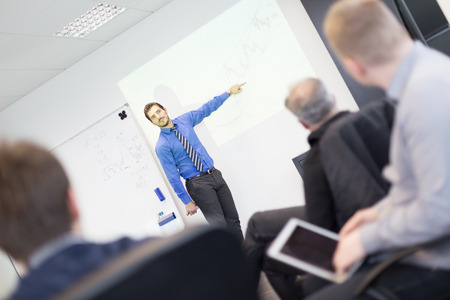 group training: Business man making a presentation at office. Business executive delivering a presentation to his colleagues during meeting or in-house business training, explaining business plans to his employees. Stock Photo