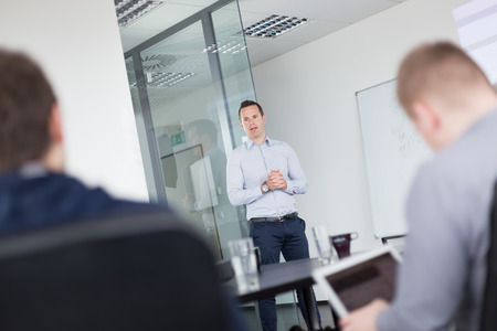 listeners: Business man making a presentation at office. Business executive delivering a presentation to his colleagues during meeting or in-house business training, explaining business plans to his employees. Stock Photo
