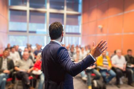 公開プレゼンテーションでのビジネス会議でスピーカー。会議ホールで聴衆。起業家クラブ。背面ビュー。水平の組成物。背景をぼかし。
