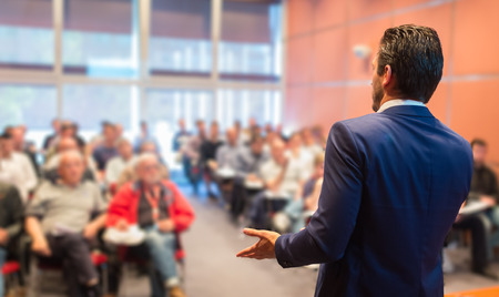 maestra ense�ando: Ponente en la Conferencia de negocios con presentaciones p�blicas. Audiencia en la sala de conferencias. Club de Emprendimiento. Vista trasera. Composici�n Horisontal. Desenfoque de fondo.