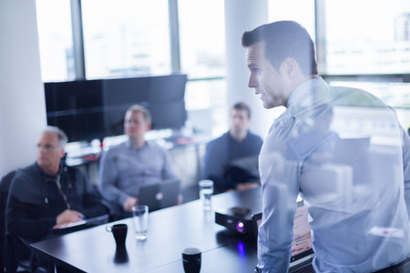 ビジネス: ビジネスの男性は、オフィスでプレゼンテーションを行います。ビジネス エグゼクティブ会議や社内のビジネス、事業計画を説明する彼の従業員にトレーニング中 写真素材